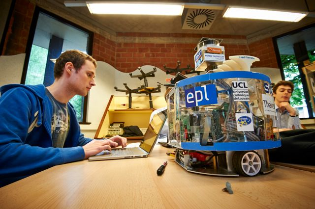 Student in front of his computer and next to a robot